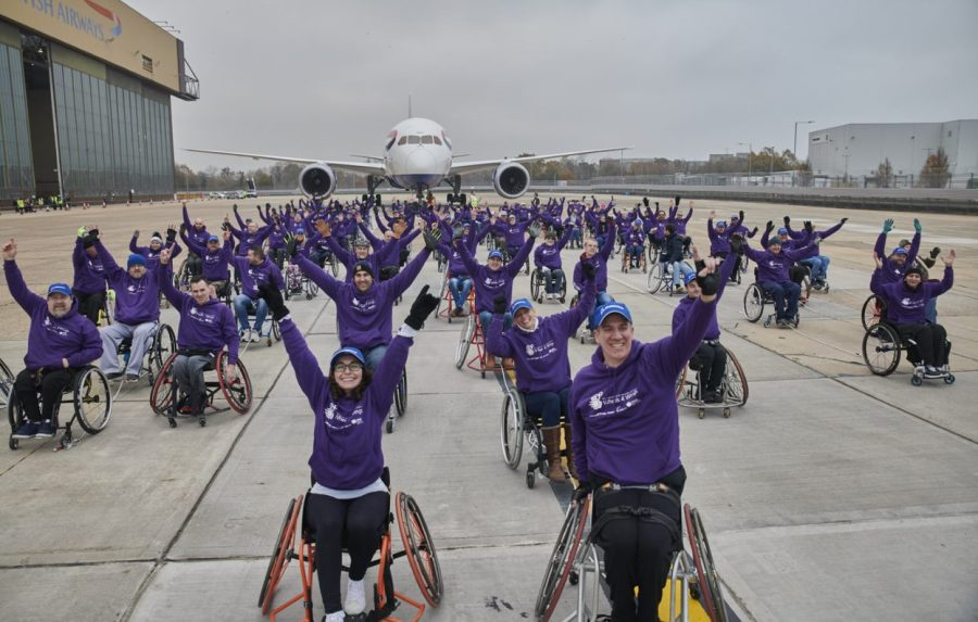 Image shows 100 people in wheelchairs pulling a plane for 100 metres