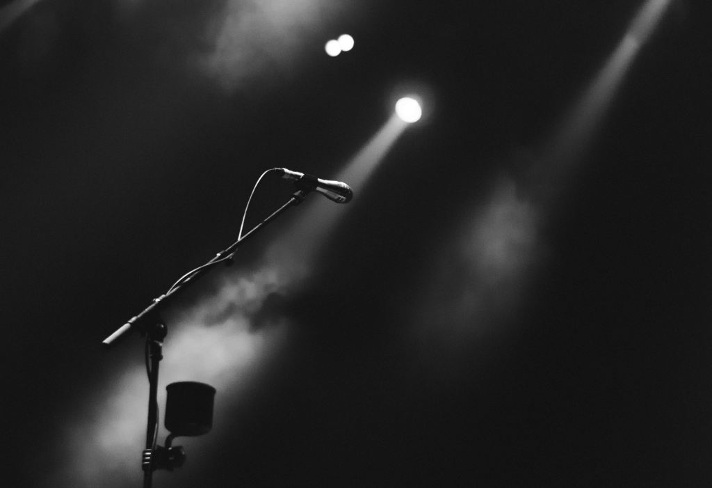 Black and white photograph of a microphone underneath a spotlight